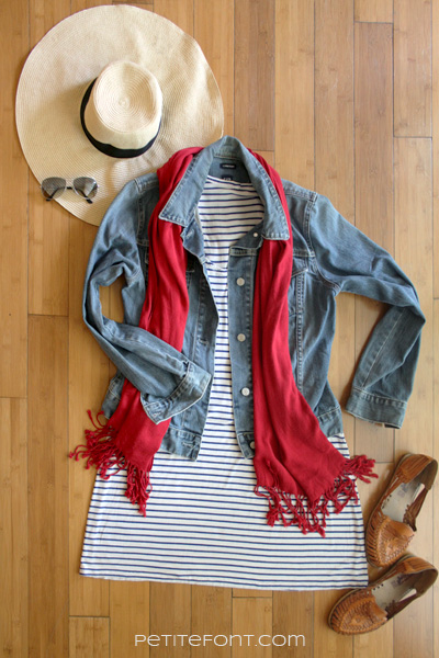 Flatlay image of how to style a jean jacket for casual day out: a large hat, sunglasses, jean jacket, striped knit dress, red scarf, and tan Mexican flat sandals