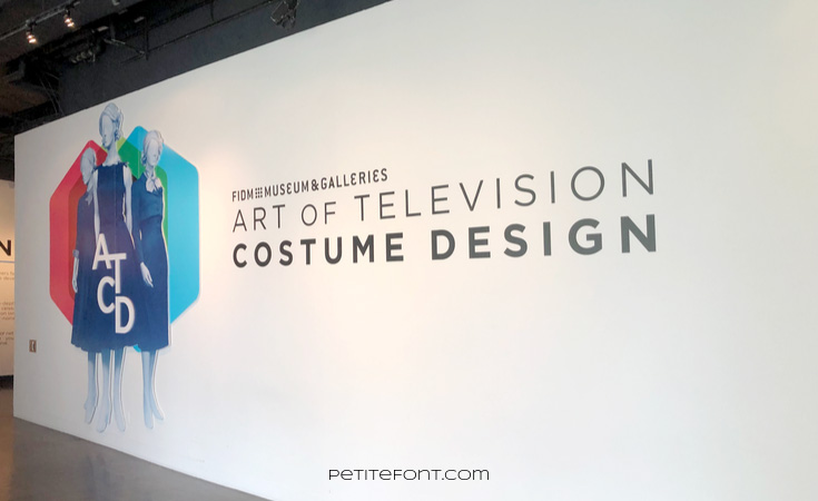 White wall with 3 fashion drawings and large text that reads FIDM Museum & Galleries Art of Television Costume Design