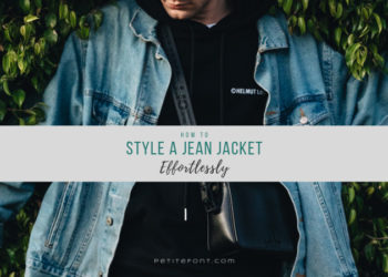 "A person in black wearing a light blue vintage denim jacket leaning against bushes looking down with text overlay that reads ""how to style a jean jacket effortlessly"" petite font dot com"