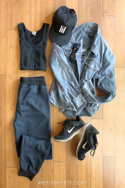 Flatlay image of how to style a jean jacket for an ultra casual day: black baseball cap, black tank top, blue joggers, jean jacket, sunglasses, and black running shoes