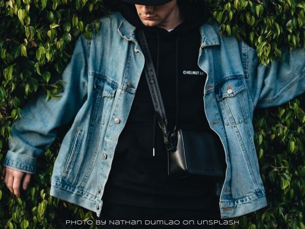 A person in black wearing a light blue vintage denim jacket leaning against bushes looking down
