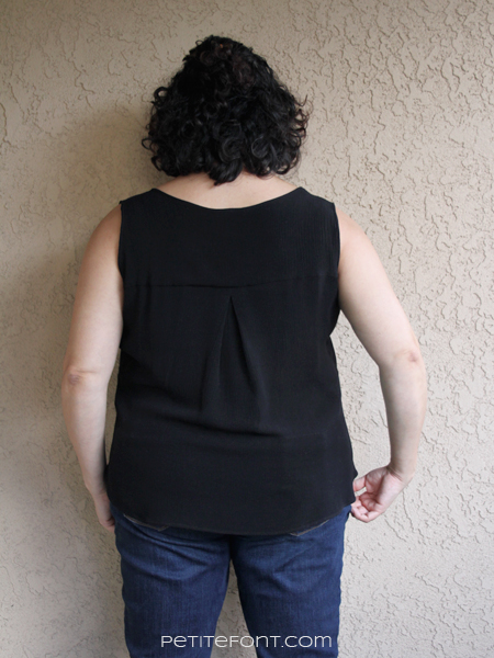 Back view of curly haired Latina in a black sleeveless Rhapsody blouse from Love Notions