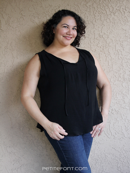 Front view of curly haired Latina in a black sleeveless Rhapsody blouse from Love Notions with her hands in her pockets