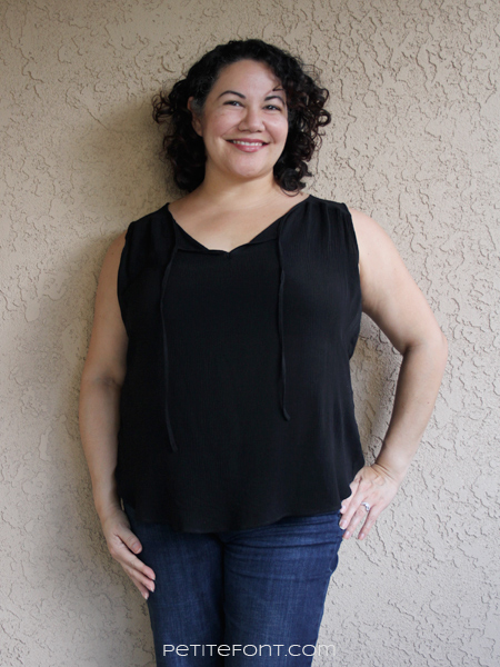 Front view of curly haired Latina in a black sleeveless Rhapsody blouse from Love Notions