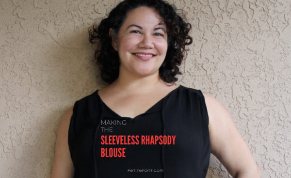 Curly haired Latina woman leaning against beige stucco wall with text overlay that reads Making the Sleeveless Rhapsody Blouse petite font dot com