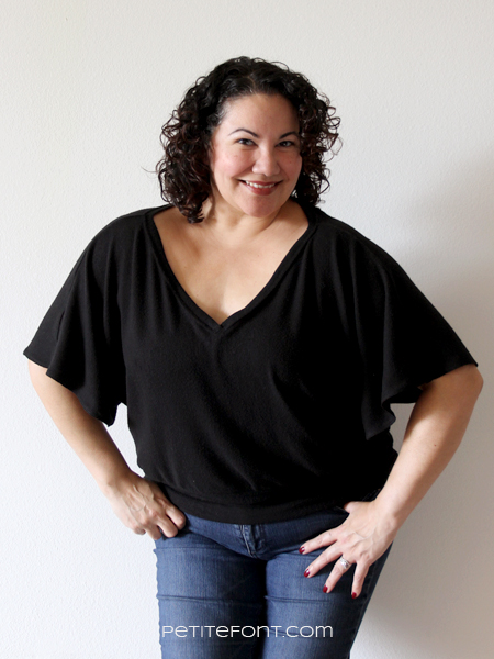 Curly haired Latina woman leaning slightly forward in front of a white wall with her hands in her jean pockets wearing a handmade black New Look 6648 sweater