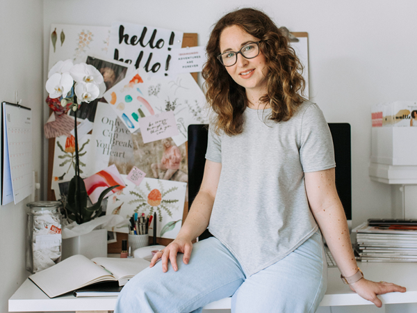 Megan Nielsen wearing glasses, a grey t-shirt, and light jeans sitting on her desk