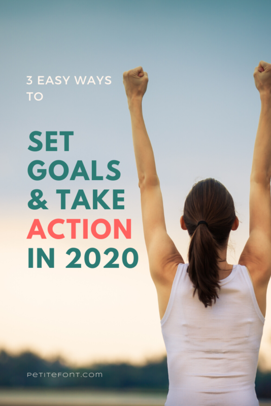 Back view of a woman in a white shirt with her hands up in a victory stance staring at the sunset with text overlay next to her that reads 3 Easy Ways to Set Goals & Take Action in 2020, petitefont.com