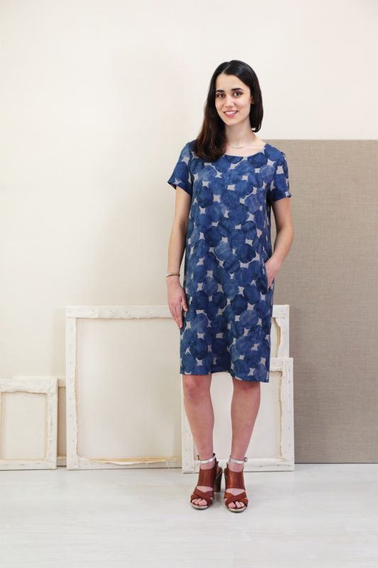Woman in front of a bunch of back of canvases wearing a blue abstract patterned Liesl + Co Gelato Dress