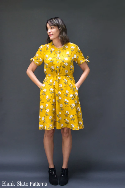 Woman against a grey background in a gold floral Blank Slate Patterns Marigold Dress