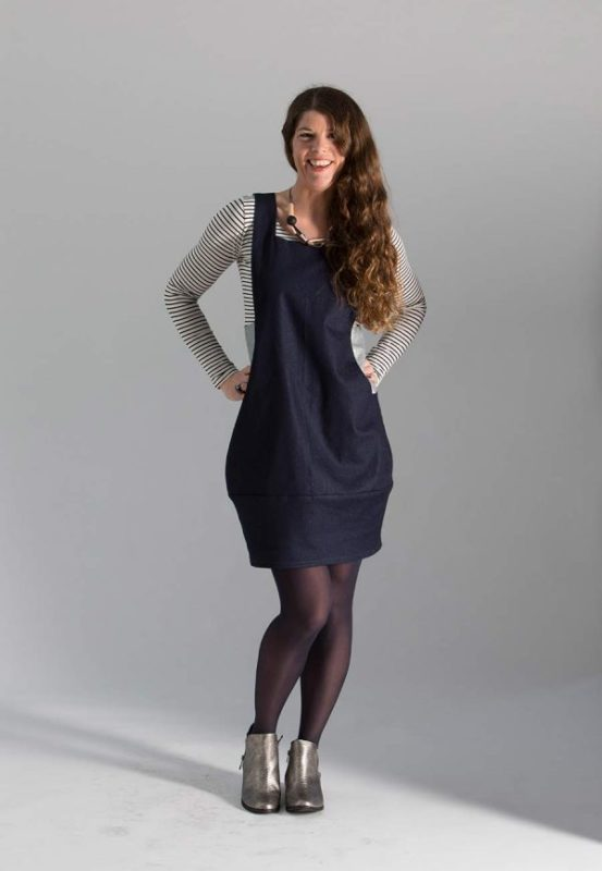 Woman against a grey background in a dark blue Sew Different Scoop Pinafore