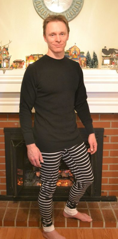 Man in front of a fire place wearing black and white striped Rad Patterns Long John Jammers