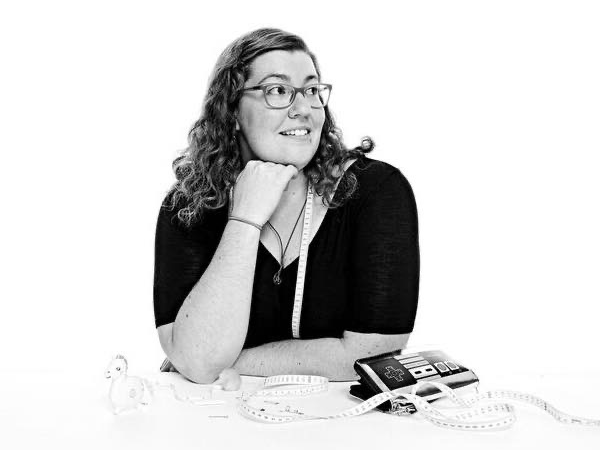 Black and white photo of Rad Pattern owner Stephanie Thiel in a dark top wearing glasses and looking off to the right while leaning against a white table with measuring tapes about and a bag that resembles an old school Nintendo controller in front of her