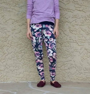 Cut off image of a person in lavender long sleeve shirt, floral Rad Patterns jammers, and dark moccasins leaning against a beige stucco wall