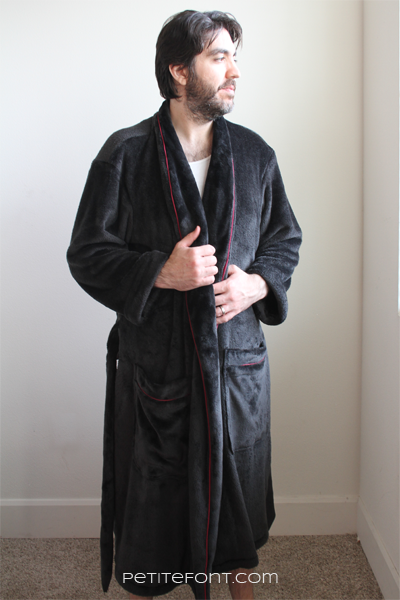 Dark haired man wearing a black robe with red piping made from Simplicity 8323 sewing pattern, he is looking off camera to the right
