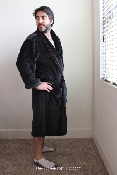 Side view of a dark haired man in a black robe with red piping made from Simplicity 8323 sewing pattern, he is looking over his shoulder