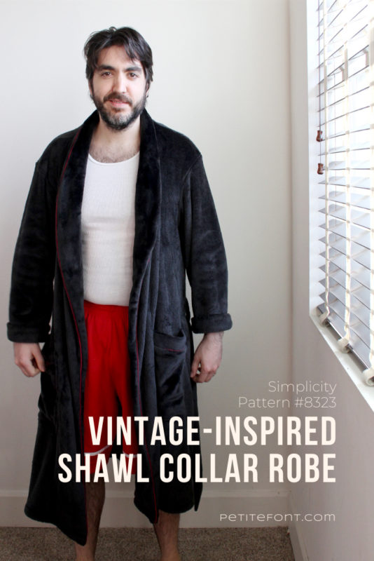 A dark haired man stands next to a window, looking slightly disheveled in an open front black robe, wearing a white tank and red basketball shorts underneath. White text overlay reads Simplicity Pattern #8323 vintage-inspired shawl collar robe, petitefont.com