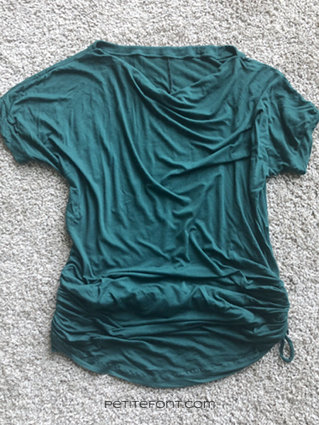 Dark green t-shirt on a light beige carpet showing first fix from the Mendy project, the hem