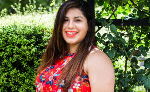Headshot of Laela Jeyne Patterns designer Marisa Ryniak in a sleeveless red floral top against green bushes
