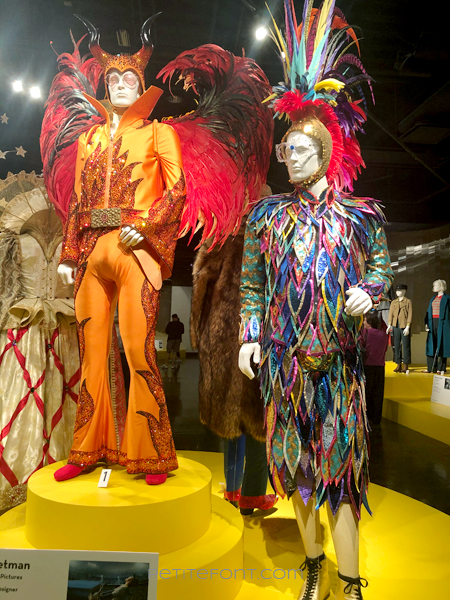 2 mannequins wearing a bright orange jumpsuit with feathers and another in a sequined feathered dress, both movie costumes from 2019's Elton John biopic Rocketman