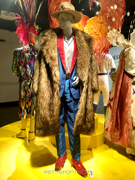A blue suit with red crystal lapels under a 3/4 length fur coat, and red crystal-covered shoes,  movie costume from 2019's Elton John biopic Rocketman
