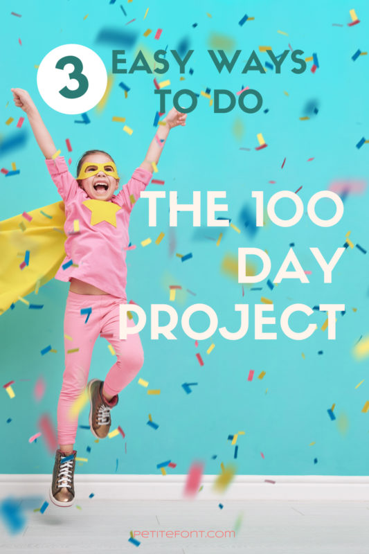 Little girl in pink PJs and a yellow cape jumping in the air while confetti falls around her. A turquoise wall is behind her. Text overlay reads 3 easy ways to do the 100 day project. PetiteFont.com