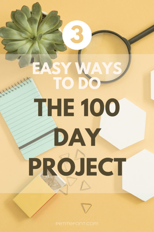 Yellow background with a plant, magnifying glass, blue notepad, white hexagons, and triangular paperclips on it. Text overlay reads 3 easy ways to do the 100 day project PetiteFont.com