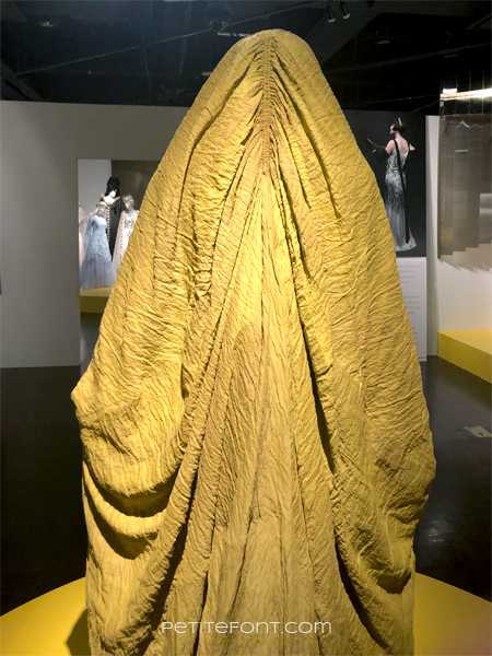 Closer view of the back of costume showing ruching around the head of the yellow Aki-Aki character from Star Wars as seen at the 2020 movie costumes exhibit at FIDM