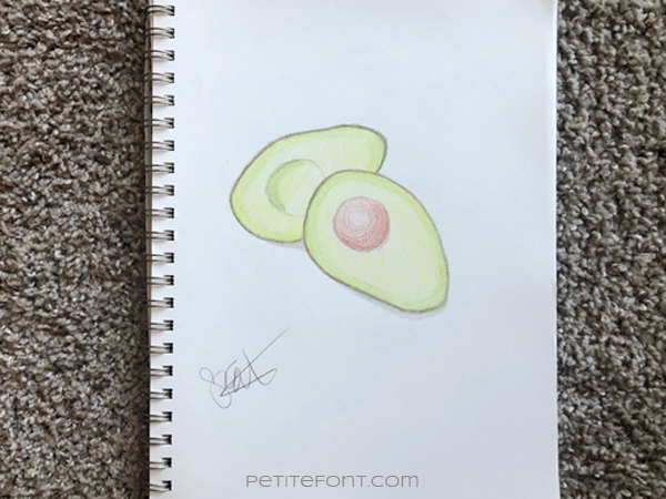Sketchbook on carpet with a page opened to a crayon drawing of an avocado split in half. Signed by the artist. Text overlay reads PetiteFont.com
