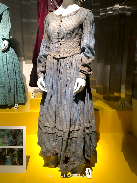 Torn and dirty pinstriped blue dress from Harriett, at the 2020 movie costumes exhibit at FIDM