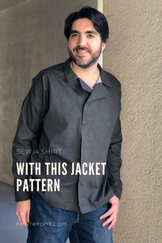 Dark haired man wearing a dark charcoal grey Ilford jacket as a shirt, with jeans, leaning up against a beige stucco wall with text overlay that reads Sew a Shirt with this Jacket Pattern, PetiteFont.com