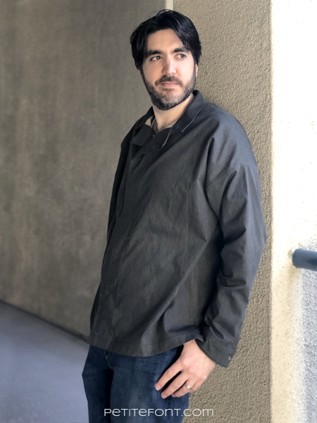 Dark haired man wearing a dark charcoal grey Ilford jacket as a shirt, with jeans, leaning up against a beige stucco wall