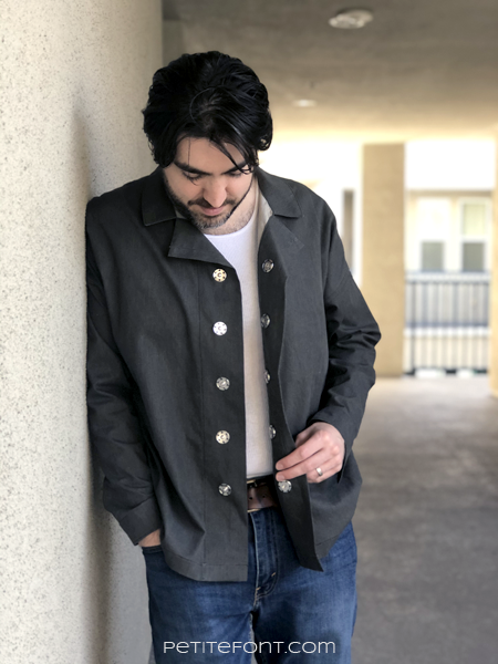 Dark haired man wearing a dark charcoal grey Ilford jacket as a shirt, open at the front to expose his undershirt, with jeans, leaning up against a beige stucco wall
