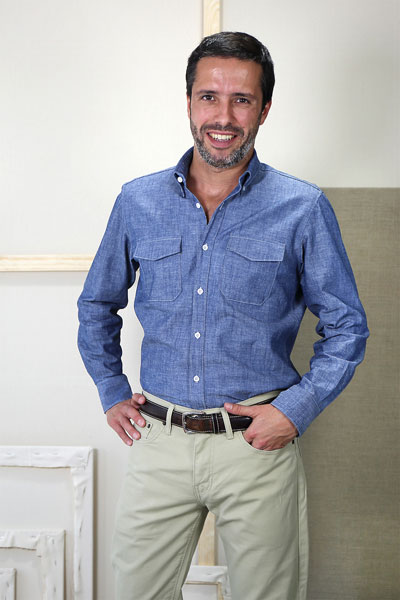 Man in a blue button up shirt tucked into khaki pants modeling the Liesl & Co men's All Day Shirt