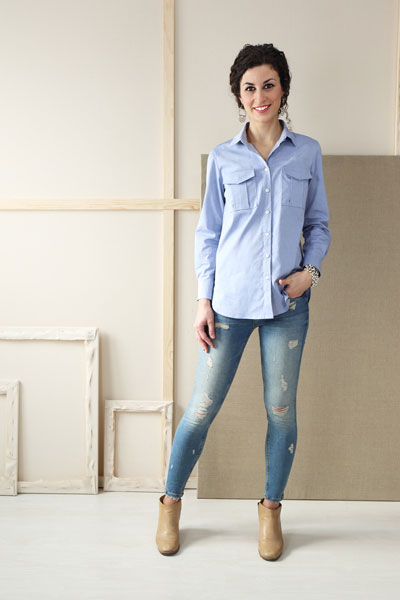 Woman in a blue button up shirt, modeling the Liesl & Co Classic shirt