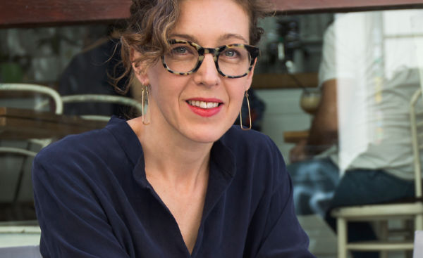 Headshot of Liesl Gibson wearing glasses, dangly earrings and a dark blue shirt