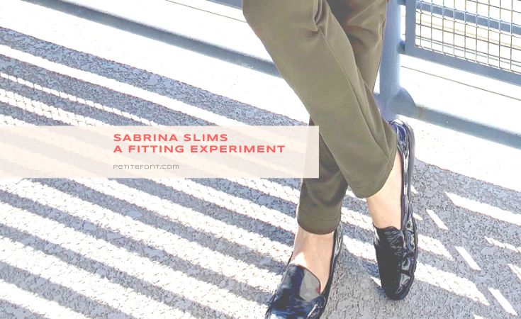 Image of person wearing olive green pants and patent leather loavers with the ankles crossed, a shadow across the ground of the railing behind them, and text overlay that reads Sabrina Slims, A Fitting Experiement, PetiteFont.com