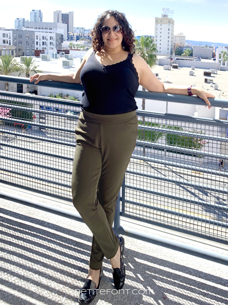 Curly haired woman wearing glasses leaning against a blue banister with a city skyline behind her. She is wearing a blank tank and olive green Sabrina Slims