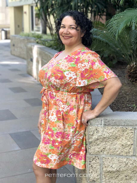Curly haired Latina in a multicolored handmade Gelato dress with a flutter sleeve