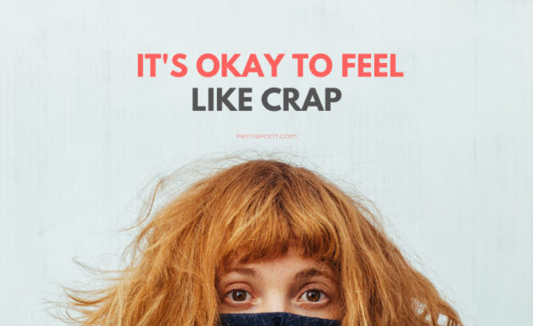 Top of a redheaded woman's face hiding in a black sweater with text above that reads It's Okay to Feel Like Crap