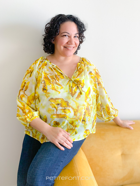 Curly haired Latina in a yellow and white handmade Roscoe blouse and jeans leaning against a yellow couch