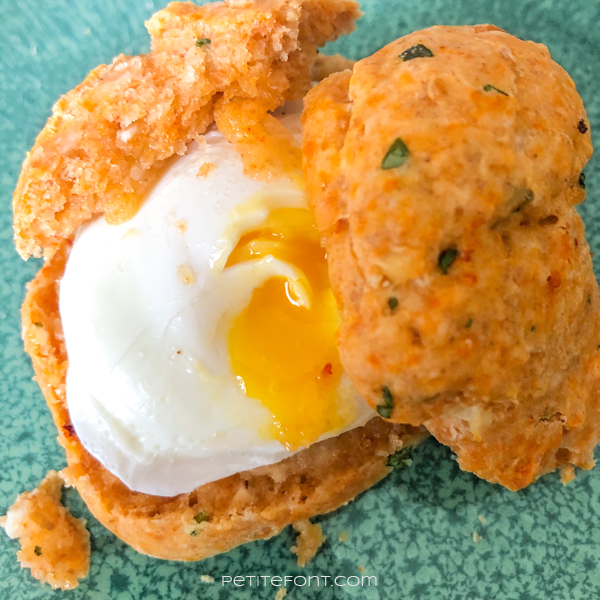 Greek Feta & Sundried Tomato Sourdough Drop Biscuit split open with a poached egg in the middle