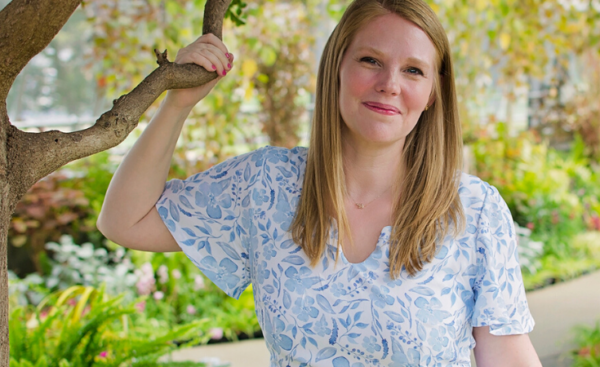 Tami Meyer's (of Love Notions) headshot depicting a blonde woman holding a tree branch wearing a blue and white floral tunic