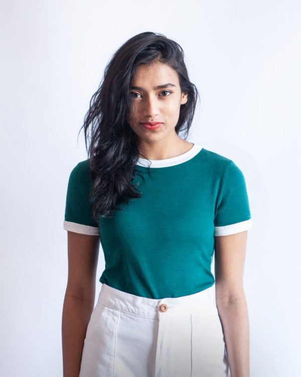 Woman in a green Rio Ringer tee with white binding