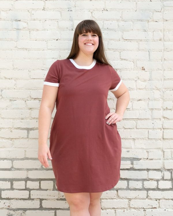 Woman in a brown Rio Ringer dress with white binding