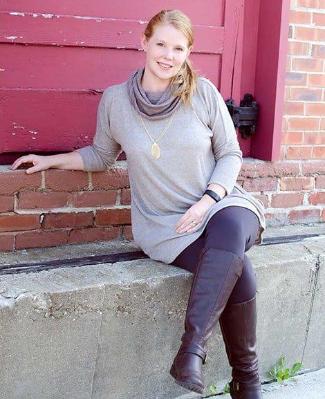 Woman in sitting on a concrete ledge wearing a grey La Bella Donna