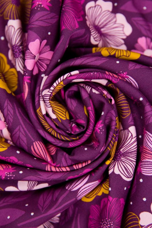 Close up view of Figo rayon fabric in Sangria floral print rolled up