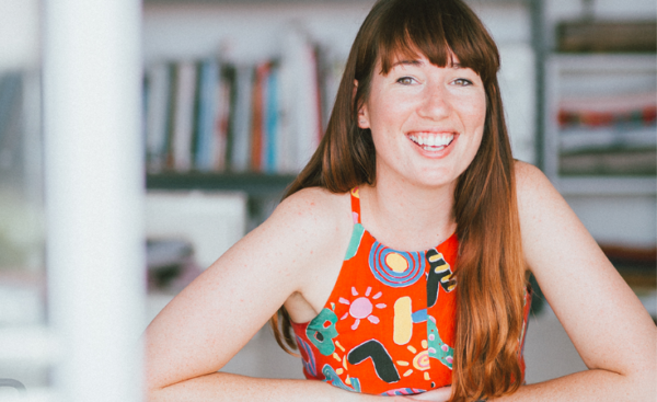 Designer Emily Hundt from In the Folds with her elbows on the table in front of her, smiling at the camera in a brightly patterned orange halter top