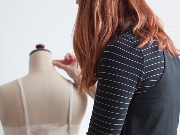 Back view of a woman in a striped black and white long sleeved shirt with her arm extended towards a dressmaking mannequin