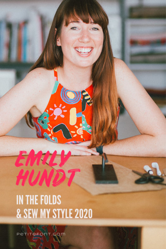 Image of a woman with her elbows on a work table in front of her, smiling at the camera in a brightly patterned orange halter top. Text overlay reads Emily Hundt, In The Folds & Sew My Style 2020, PetiteFont.com